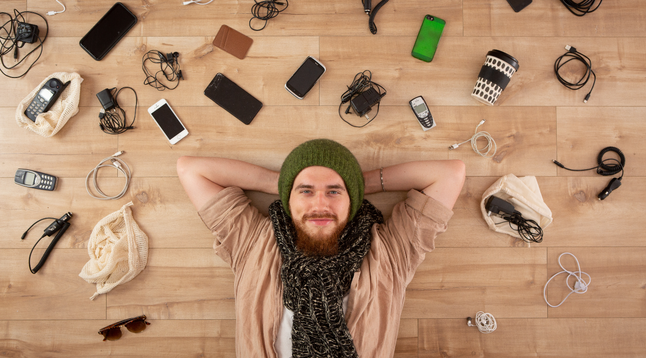 Person laying down surrounded by phones.
